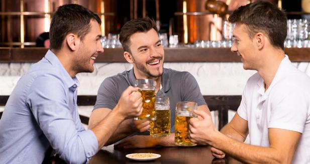 Mężczyźni w pubie pijący piwo